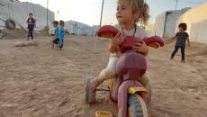 Despite the baking summer sun, IDP kids play on sand, sunk in dust