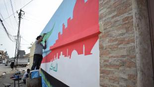 شابان يسعيان لتلوين مدينة الموصل