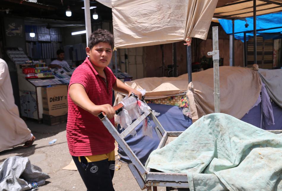Adım Aziz İzzedin. 15 yaşındayım. Hergün saat 08.00'da evden çıkıyorum. Selahaddin Caddesi'nde (Han Hurma) el arabasıyla vatandaşların eşyalarını taşıyorum. Bazı günler 6 bin dinar kazanıyorum.