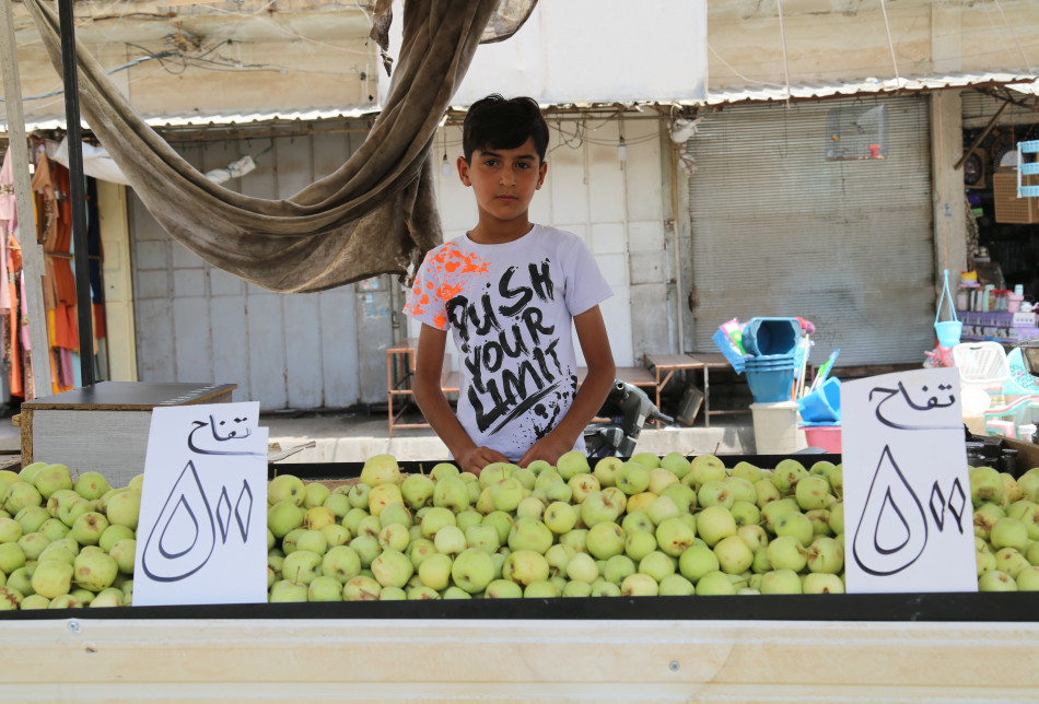 Adım Ercan Adil, 12 yaşındayım. Beşinci sınıfta öğrenciyim. Tatilde veya başka zamanlarda babama yardım ediyorum. Habat Köprüsü'nde sebze ve meyve satıyorum. Günde 5 bin dinar kazanıyorum.